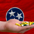Stock Photo: Holding pills in hand in front of tennessee us state flag
