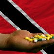 Stock Photo: Holding pills in hand in front of trinidad tobago national flag