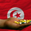 Stock Photo: Holding pills in hand in front of tunisinational flag