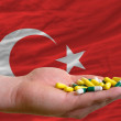 Stock Photo: Holding pills in hand in front of turkey national flag