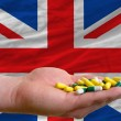 Stock Photo: Holding pills in hand in front of great britain national flag