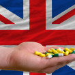 Holding pills in hand in front of great britain national flag - Zdjęcie stockowe