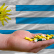 Stock Photo: Holding pills in hand in front of uruguay national flag