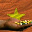 Stock Photo: Holding pills in hand in front of vietnam national flag