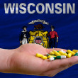 Holding pills in hand in front of wisconsin us state flag - Stock Photo