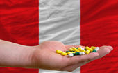 Holding pills in hand in front of peru national flag — Stock Photo
