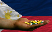 Holding pills in hand in front of philippines national flag — Stock Photo