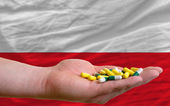 Holding pills in hand in front of poland national flag — Stock Photo