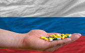 Holding pills in hand in front of russia national flag — Stock Photo