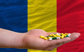 Holding pills in hand in front of romania national flag — Stock Photo