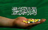 Holding pills in hand in front of saudi arabia national flag — Stock Photo