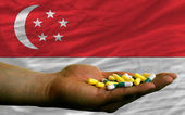 Holding pills in hand in front of singapore national flag — Stock Photo