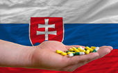 Holding pills in hand in front of slovakia national flag — Stock Photo