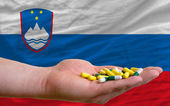 Holding pills in hand in front of slovenia national flag — Stock Photo