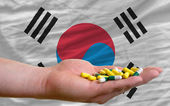 Holding pills in hand in front of south korea national flag — Stock Photo