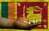 Holding pills in hand in front of sri lanka national flag — Stock Photo
