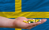 Holding pills in hand in front of sweden national flag — Stock Photo