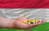 Holding pills in hand in front of tajikistan national flag — Stock Photo
