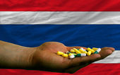 Holding pills in hand in front of thailand national flag — Stock Photo