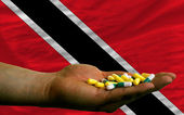 Holding pills in hand in front of trinidad tobago national flag — Stock Photo