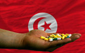 Holding pills in hand in front of tunisia national flag — Stock Photo