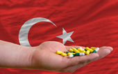 Holding pills in hand in front of turkey national flag — Stock Photo