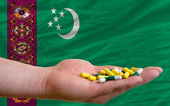 Holding pills in hand in front of turkmenistan national flag — Stock Photo