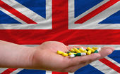 Holding pills in hand in front of great britain national flag — Stock Photo