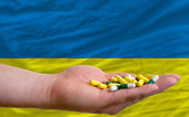 Holding pills in hand in front of ukraine national flag — Stock Photo