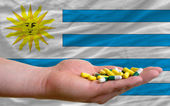 Holding pills in hand in front of uruguay national flag — Stock Photo