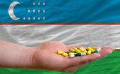 Holding pills in hand in front of uzbekistan national flag — Stock Photo