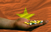Holding pills in hand in front of vietnam national flag — Stock Photo