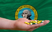 Holding pills in hand in front of washington us state flag — Stock Photo