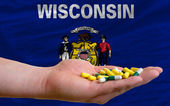 Holding pills in hand in front of wisconsin us state flag — Stock Photo