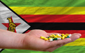Holding pills in hand in front of zimbabwe national flag — Stock Photo