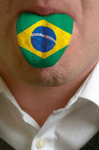 Man tongue painted in brazil flag symbolizing to knowledge to sp — Stock Photo