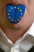 Man tongue painted in europe flag symbolizing to knowledge to sp — Stock Photo