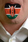 Man tongue painted in kenya flag symbolizing to knowledge to spe — Stock Photo