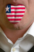 Man tongue painted in liberia flag symbolizing to knowledge to s — Stock Photo