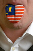 Man tongue painted in malaysia flag symbolizing to knowledge to — Stock Photo