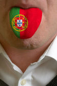 Man tongue painted in portugal flag symbolizing to knowledge to — Stockfoto