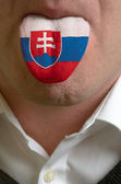 Man tongue painted in slovakia flag symbolizing to knowledge to — Stock Photo