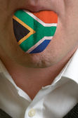 Man tongue painted in south africa flag symbolizing to knowledge — Stock Photo