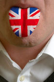 Man tongue painted in gunited kingdom flag symbolizing to knowle — Stock Photo