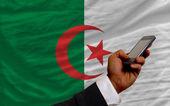 Telefone celular na primeira bandeira nacional da argélia — Fotografia Stock