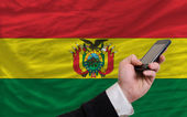 Cell phone in front national flag of bolivia — Stock Photo