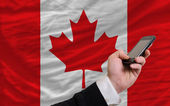 Cell phone in front national flag of canada — Stock Photo