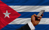 Cell phone in front national flag of cuba — Stock Photo