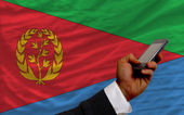 Cell phone in front national flag of of eritrea — Stock Photo