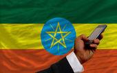 エチオピアの国旗はフロントでの携帯電話 — ストック写真